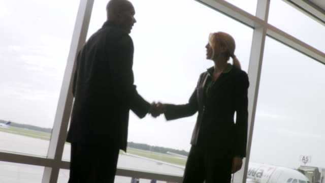 MS TU Man and woman meet and shake hand on airport / Jacksonville, FL, United States
