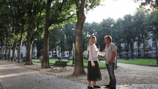uomo e donna si incontrano nel parco urbano - incontro romantico video stock e b–roll