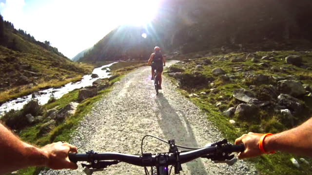 man and woman pov mountain bike on the alps - digital camcorder stock videos & royalty-free footage