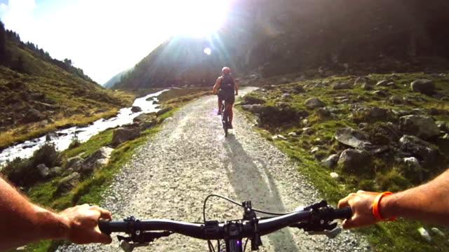 Man and Woman POV mountain bike on the Alps