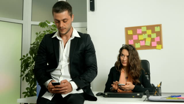 Man and woman office workers using their smart phones on their workplace
