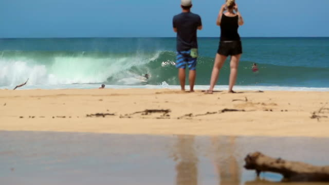 man and woman on a beach taking photos of a surfer catching a wave - {{relatedsearchurl('capsule pipeline')}} stock videos and b-roll footage