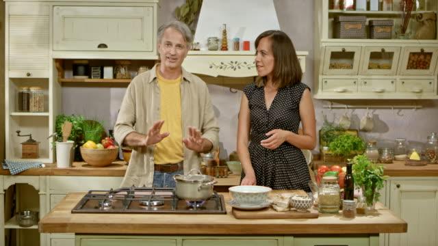 vídeos y material grabado en eventos de stock de ld de hombre y mujer en una cocina show hablando sobre ingredientes y preparación de alimentos - exhibir