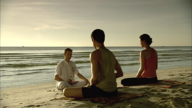 ws ds man and woman on beach with meditation instructor, hua hin, prachuap khiri khan, thailand - man sitting cross legged stock videos & royalty-free footage