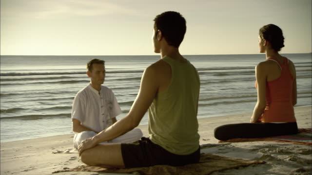 vidéos et rushes de ws ds man and woman on beach with meditation instructor, hua hin, prachuap khiri khan, thailand - bouddhisme