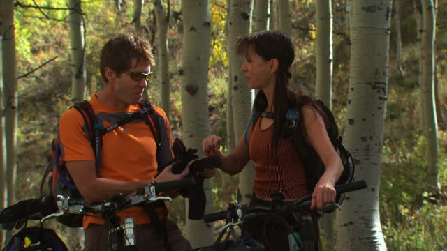 man and woman on mountain bikes - see other clips from this shoot 1151 stock videos and b-roll footage