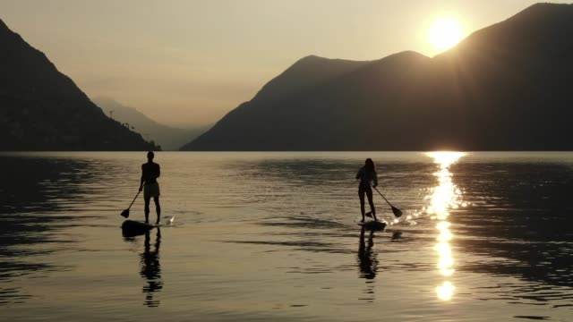 man and woman on paddle boards on a lake - panning stock videos & royalty-free footage