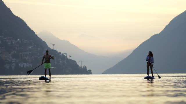vídeos y material grabado en eventos de stock de hombre y mujer en tablas de paddle en un lago - generación z