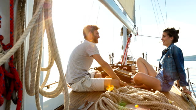 vídeos de stock e filmes b-roll de man and woman on sailboat - cross legged