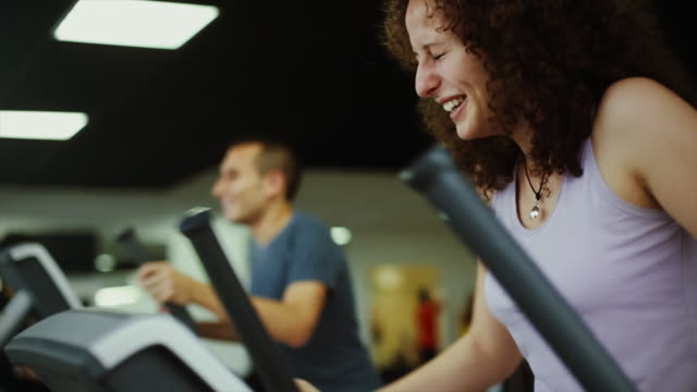 man and woman on the cardio machine: hard training in the gym - man and machine stock videos & royalty-free footage
