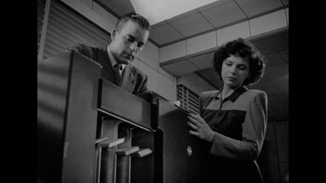 1948 a man and woman operate an office machine - film noir style stock videos and b-roll footage