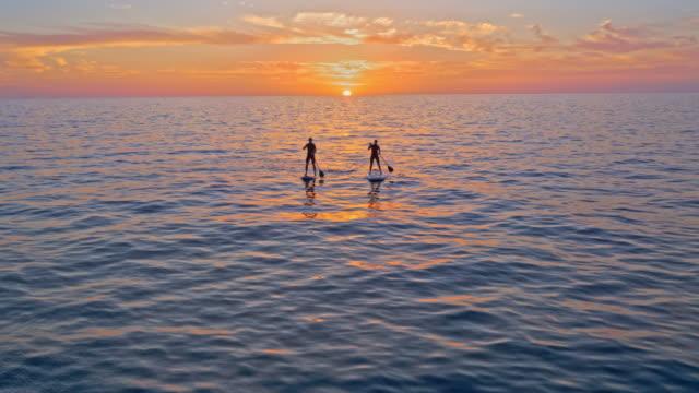 stockvideo's en b-roll-footage met luchtfoto man en vrouw peddelen hun sups bij zonsondergang - middellandse zee