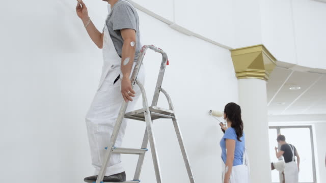 ms tu man and woman painting wall / london, england, united kingdom - house painter stock videos and b-roll footage
