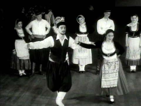 man and woman perform a traditional greek folk dance at a rehearsal for the 1954 international dance festival in london. - traditional ceremony stock videos & royalty-free footage