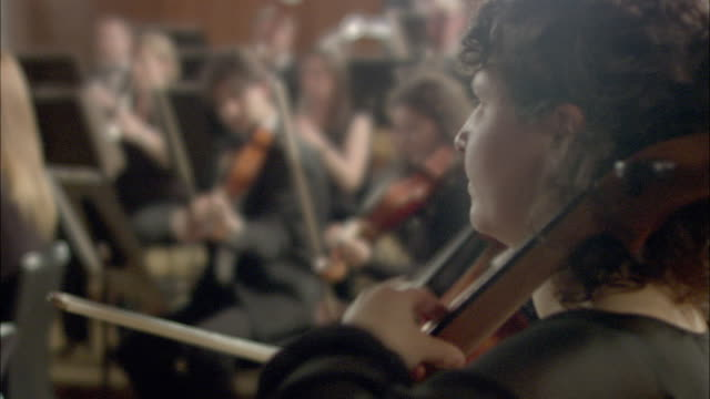 MS R/F Man and woman performing cellos in orchestra, musicians in background / London, United Kingdom