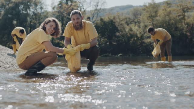 vídeos de stock e filmes b-roll de man and woman picking up trash from water - sem higiene
