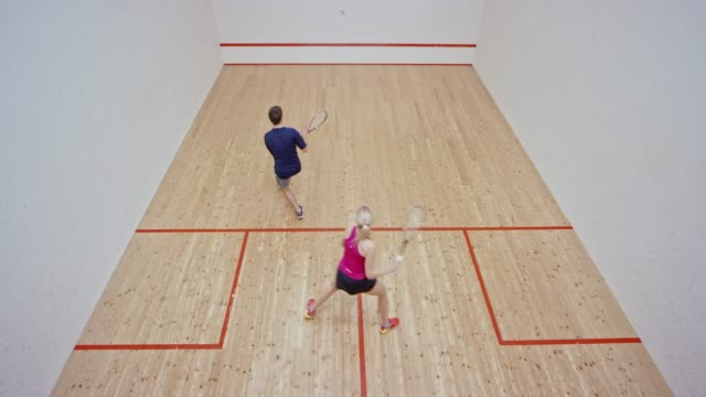 man and woman playing a game of squash - squash sport stock videos & royalty-free footage
