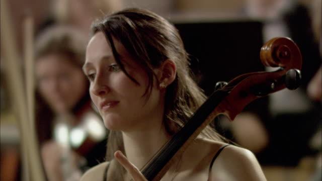 cu r/f man and woman playing cellos in orchestra / london, united kingdom - 30 34 ��r bildbanksvideor och videomaterial från bakom kulisserna