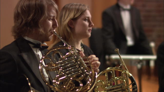 MS Man and woman playing French horns in orchestra / London, United Kingdom