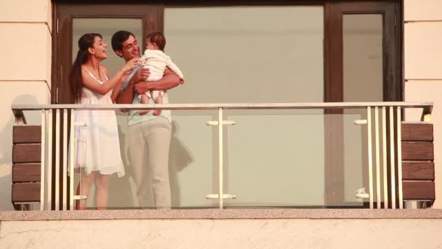 vídeos de stock, filmes e b-roll de man and woman playing with their baby  - vida de bebê