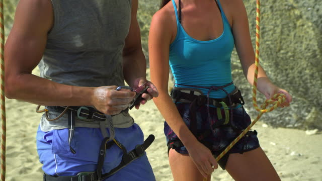 ms man and woman preparing rock climbing equipment, woman tying rope around harness, looking up and discussing / krabi, thailand - climbing equipment stock videos & royalty-free footage