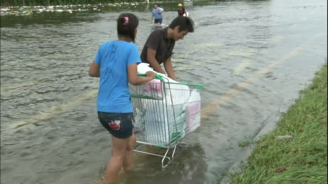 a man and woman push a shopping cart on a flooded ayutthaya street - push cart stock videos & royalty-free footage