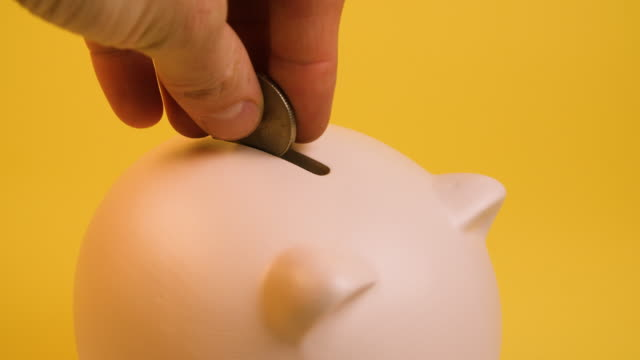 a man and woman put coins into a piggy bank - responsibility stock videos & royalty-free footage