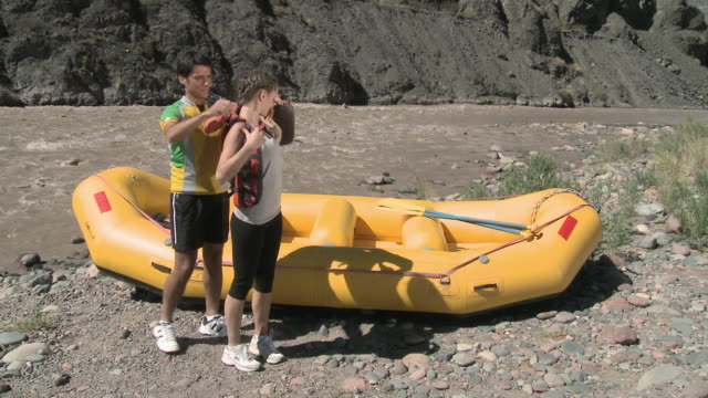 stockvideo's en b-roll-footage met man and woman putting on lifejackets ready for rafting  - argentijnse etniciteit