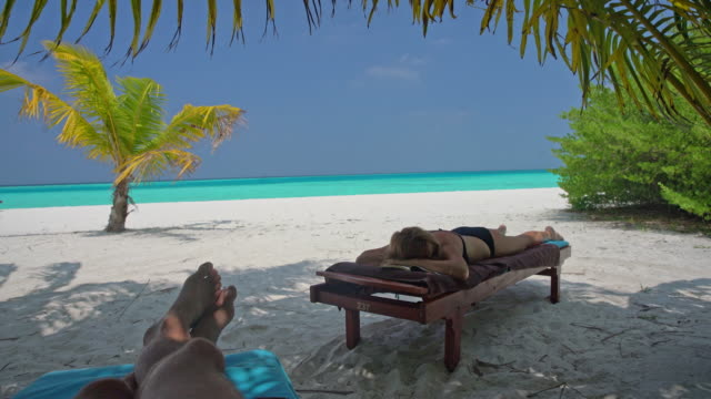 vídeos de stock e filmes b-roll de ms man and woman relaxing,napping on lounge chairs on idyllic,tropical ocean beach,maldives - com sombra