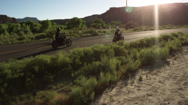 Man and woman ride motorcycles down desert highway, aerial view