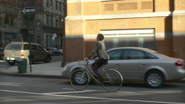 WS TS Man and woman riding bicycles on bike lane of street in Tribeca / New York City, New York, USA