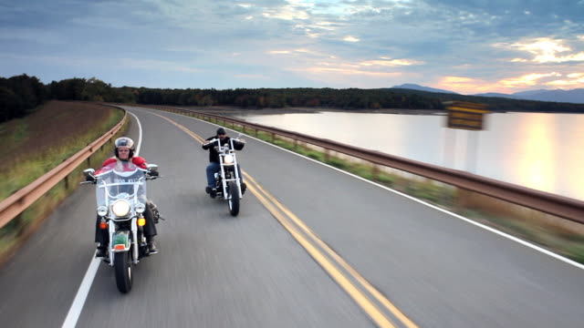 MS PAN POV Man and woman riding motorcycles on country road with along lake and mountains at sunset / West Hurley, New York, United States