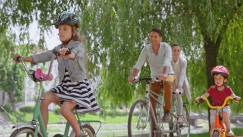 slo mo ts man och kvinna ridning på en tandemcykel och deras två barn rida sina cyklar tillsammans med dem i parken - park bildbanksvideor och videomaterial från bakom kulisserna