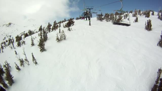ws pov man and woman riding on ski lift  / mammoth lakes, california, united states - mammoth lakes video stock e b–roll