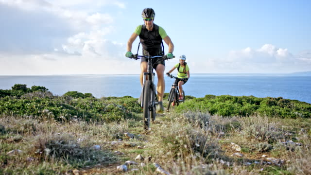 man and woman riding their mountain bikes up a hill by the sea on a sunny day - mountain bike stock videos & royalty-free footage