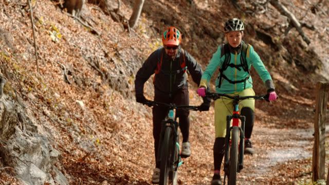 男と女の秋に日当たりの良い林道をマウンテン バイクに乗って - サイクリングロード点の映像素材/bロール