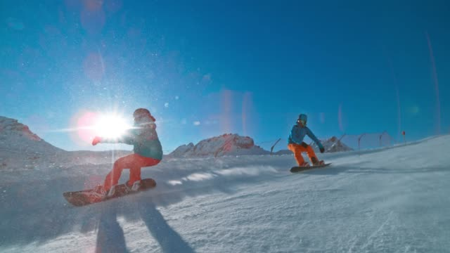 slo mo ts man and woman riding their snowboards down a sunny mountain piste - snowboard video stock e b–roll