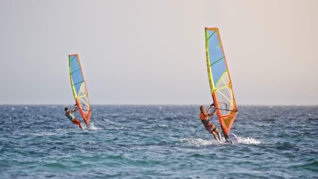 stockvideo's en b-roll-footage met slo mo man en vrouw rijden hun kanoverhuur in zon - windsurfen
