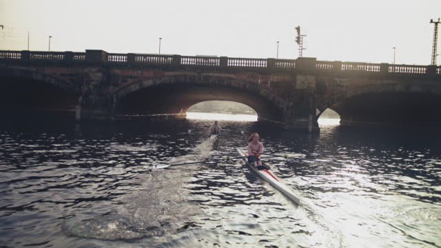 man and woman rowing boat in river - sculling stock videos & royalty-free footage