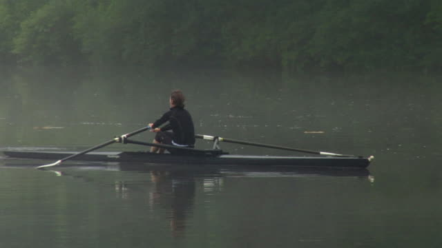ws pan man and woman rowing in single sculls on the connecticut river at dawn/ hanover, new hampshire, usa - scull stock videos & royalty-free footage