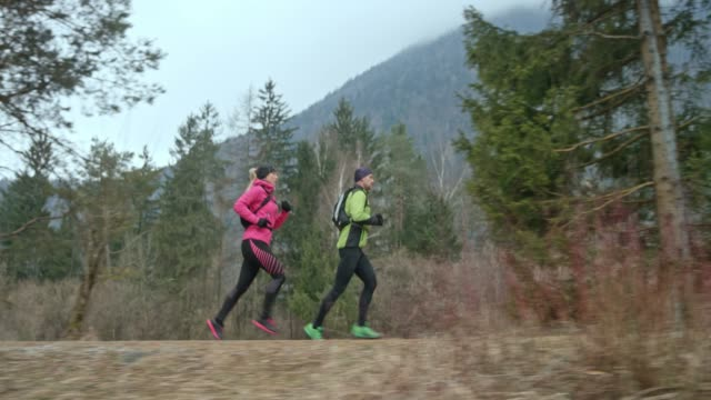 TS Man and woman running on a path in nature on a cold day