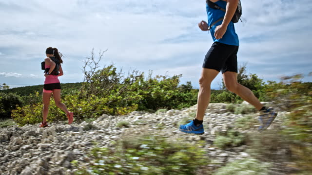 TS Man and woman running on a rocky trail down a mountain in sunshine