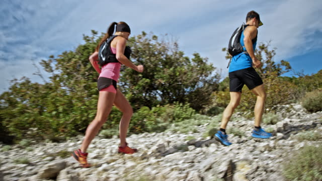 ts man and woman running on a rocky trail on a sunny day - sun visor stock videos & royalty-free footage