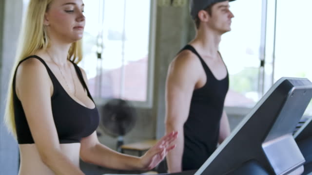 man and woman running on treadmill in gym - treadmill stock videos & royalty-free footage