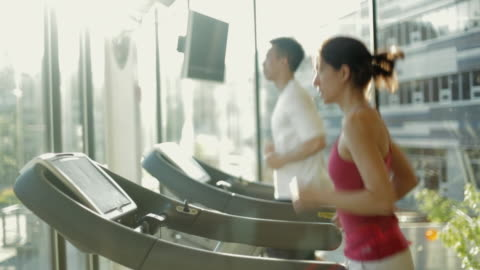 ms ds man and woman running treadmills cardio workout exercise in gym / vancouver, british columbia, canada - fitness stock videos & royalty-free footage