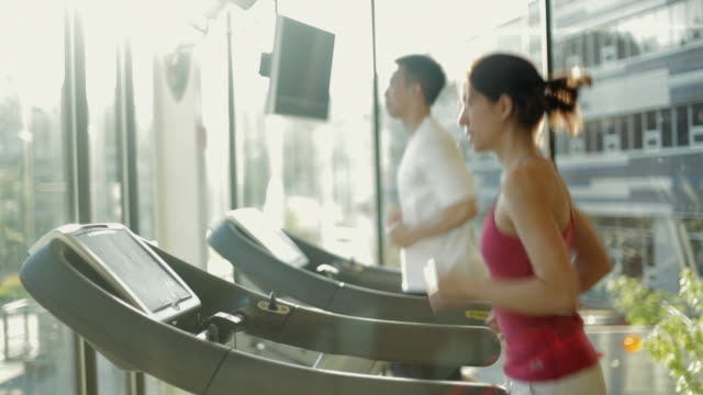 ms ds man and woman running treadmills cardio workout exercise in gym / vancouver, british columbia, canada - träna bildbanksvideor och videomaterial från bakom kulisserna