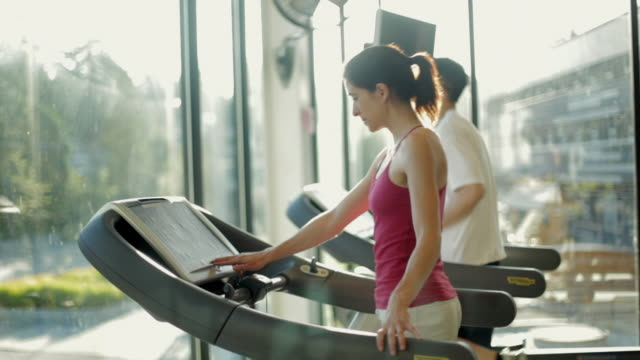 MS DS Man and woman running treadmills cardio workout exercise in gym / Vancouver, British Columbia, Canada