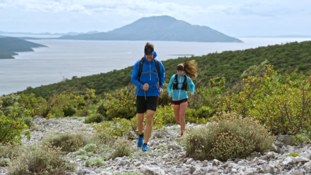man and woman running up the rocky mountain trail with a beautiful view of the sea - sun visor stock videos & royalty-free footage