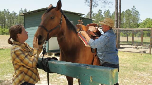 vidéos et rushes de ms man and woman saddling horse / madison, florida, usa - couleur et motif du pelage