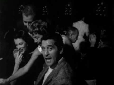 Man and woman seated at table in nightclub audience / men shake hands